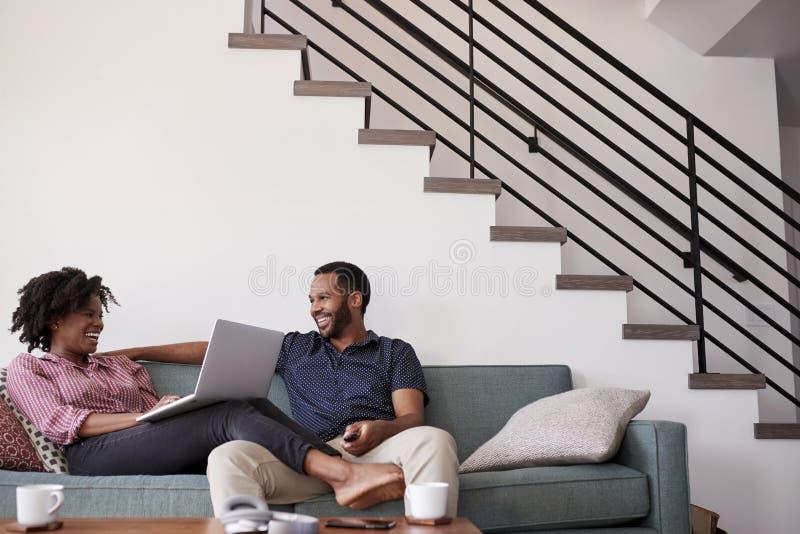 Couples se reposant sur Sofa At Home With Woman à l'aide de l'ordinateur portable image stock