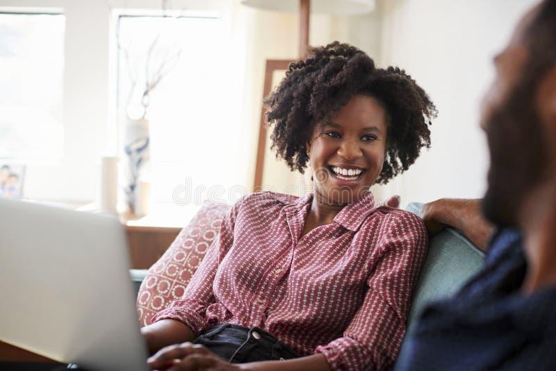 Couples se reposant sur Sofa At Home With Woman à l'aide de l'ordinateur portable photographie stock