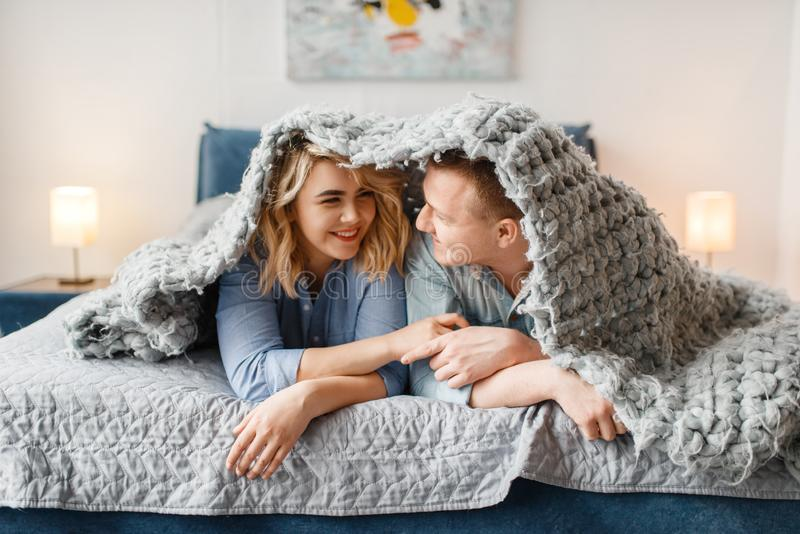 Couples se situant dans le lit, jetant un coup d'oeil de dessous la couverture photo libre de droits