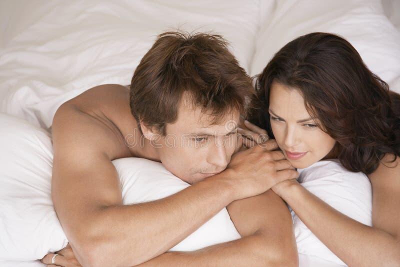 Couples se situant dans le lit regardant loin photo libre de droits