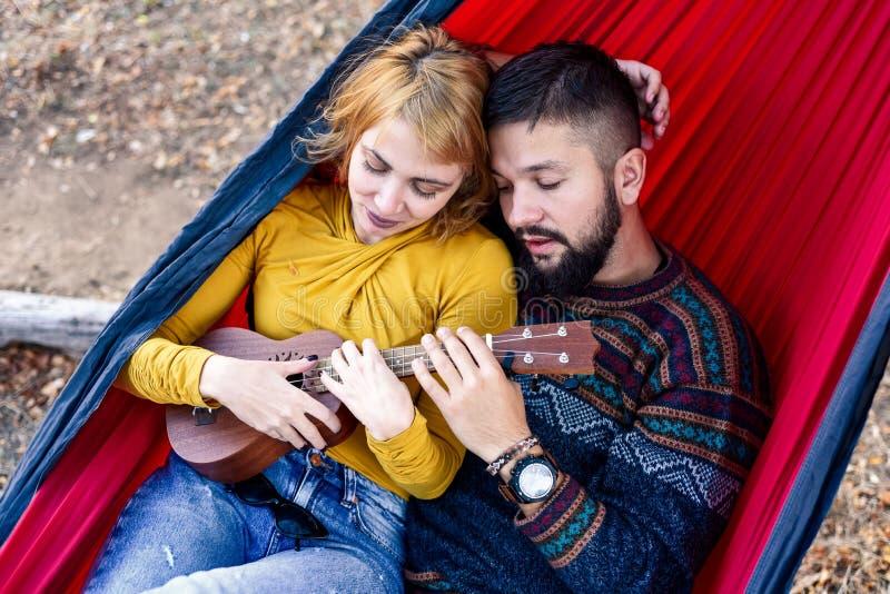 Couples se situant dans un hamac sur un pique-nique photos libres de droits