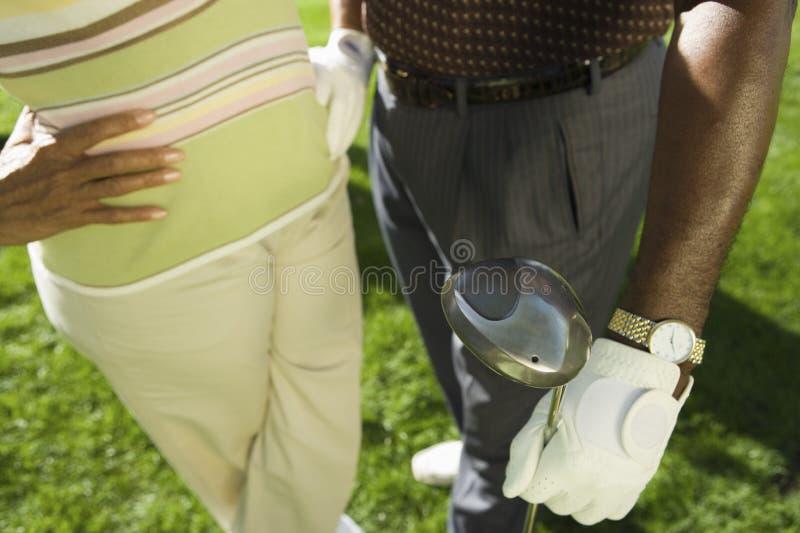 Couples se tenant avec le club de golf photos stock