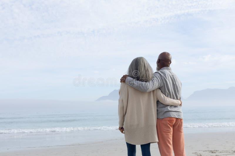 Couples se tenant sur la plage photographie stock libre de droits