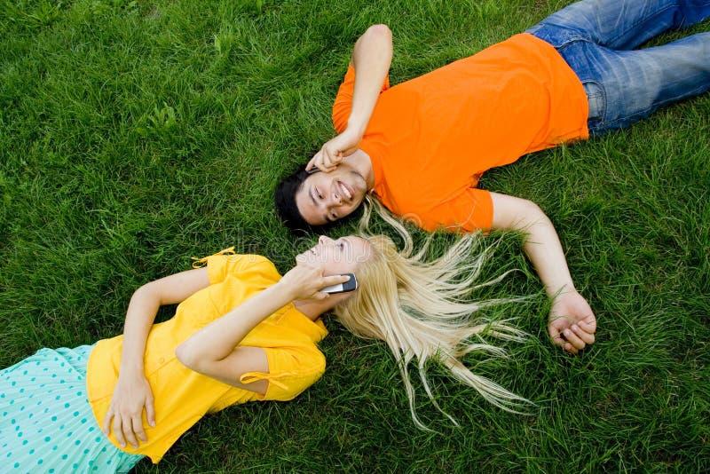 Couples se trouvant sur l'herbe photo stock