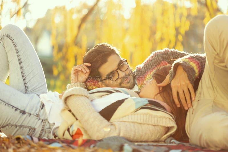 Couples se trouvant sur une couverture de pique-nique photo stock