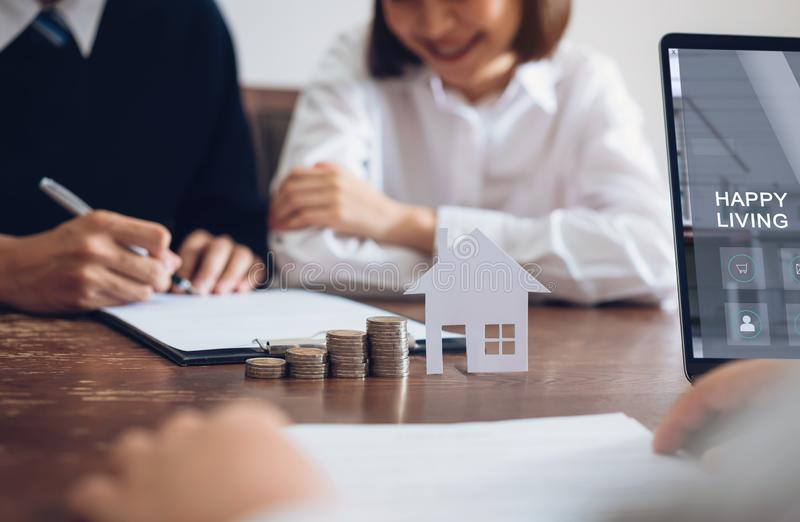 Couples signed a contract to buy a house from the broker. Coin to stack money and model house placed on the table, financial Business Growth royalty free stock photo