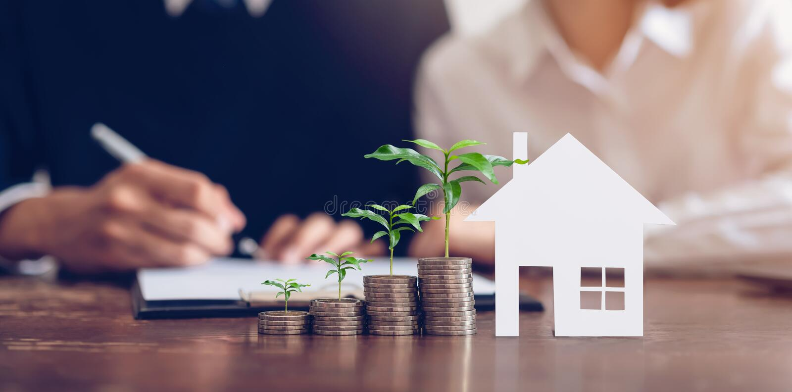 Couples signed a contract to buy a house from the broker. Coin to stack money and model houses placed on the table. Couples signed a contract to buy a house stock photos