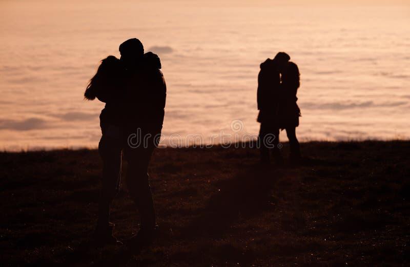 Couples silhouettés embrassant au-dessus du brouillard d'inversion image libre de droits