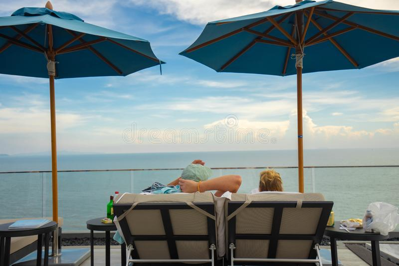 Couples sitting together by the swimming pool. Vacation and relaxation concepts.  stock photo