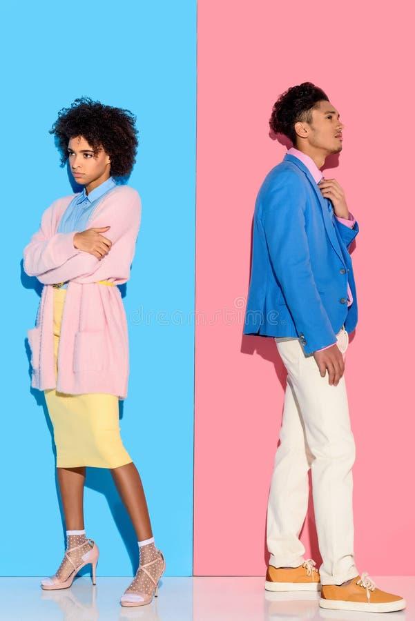Couples songeurs se tenant dans la distance de l'un l'autre sur le rose et le bleu image stock