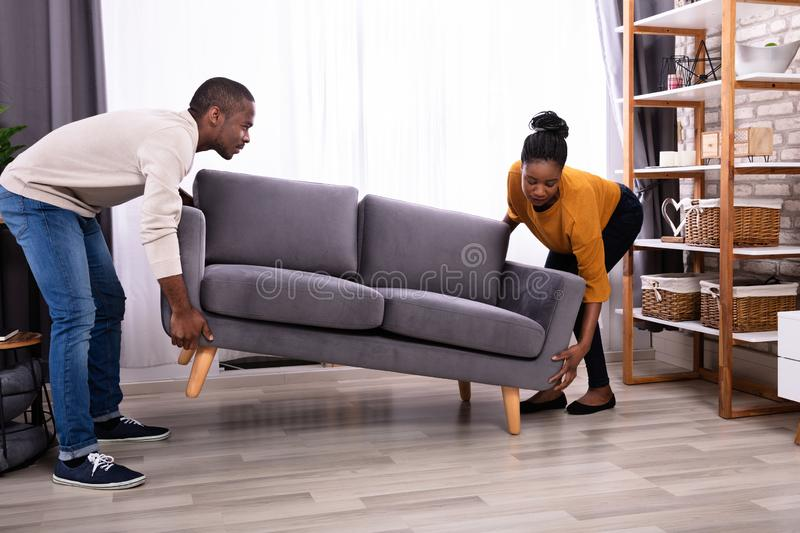 Couples soulevant Sofa In Living Room image stock