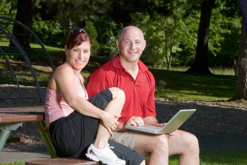 Couples souriant au stationnement - horizontal images libres de droits