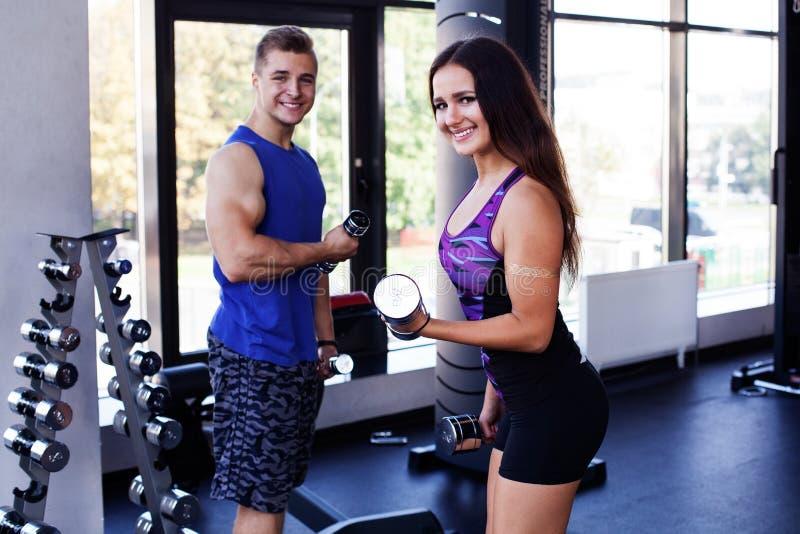Couples sportifs démontrant des biceps photos stock