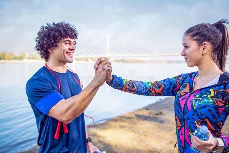 Couples sportifs donnant hauts cinq entre eux après séance d'entraînement images libres de droits