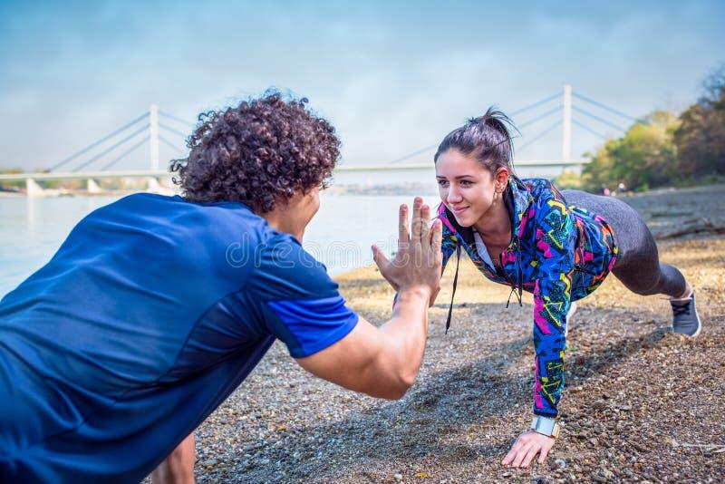 Couples sportifs donnant la haute cinq entre eux tout en faisant soulevez photos libres de droits