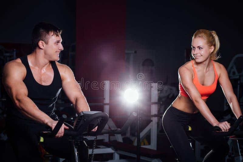 Couples sportifs exerçant à la forme physique le vélo d'exercice sur un gymnase foncé photographie stock