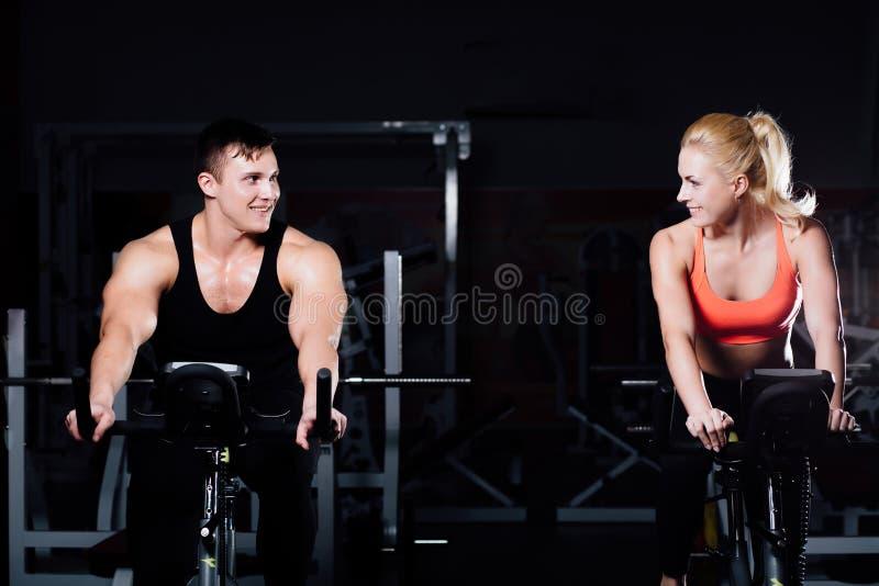 Couples sportifs exerçant à la forme physique le vélo d'exercice sur un gymnase foncé photos stock