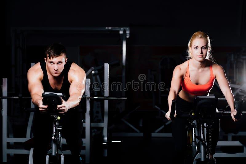 Couples sportifs exerçant à la forme physique le vélo d'exercice sur un gymnase foncé image libre de droits