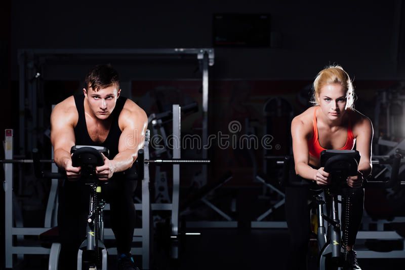 Couples sportifs exerçant à la forme physique le vélo d'exercice sur un gymnase foncé images libres de droits