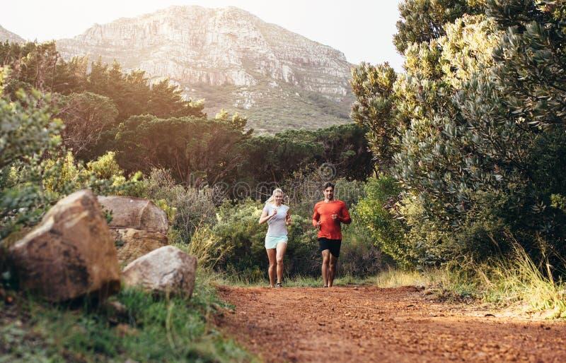 Couples sportifs fonctionnant ensemble en parc images stock