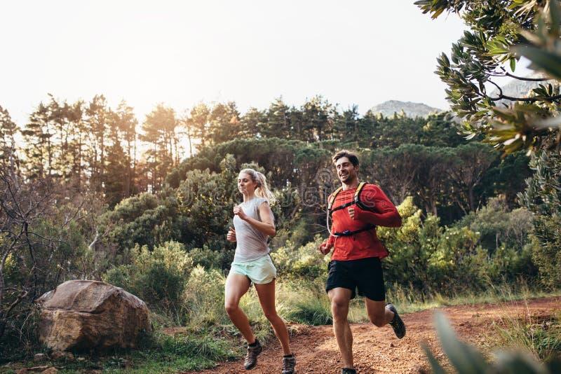 Couples sportifs fonctionnant ensemble en parc photographie stock