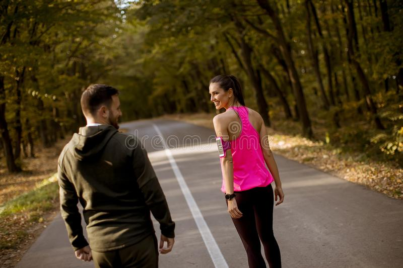 Couples sportifs fonctionnant ensemble sur la tra?n?e de for?t en automne photo stock