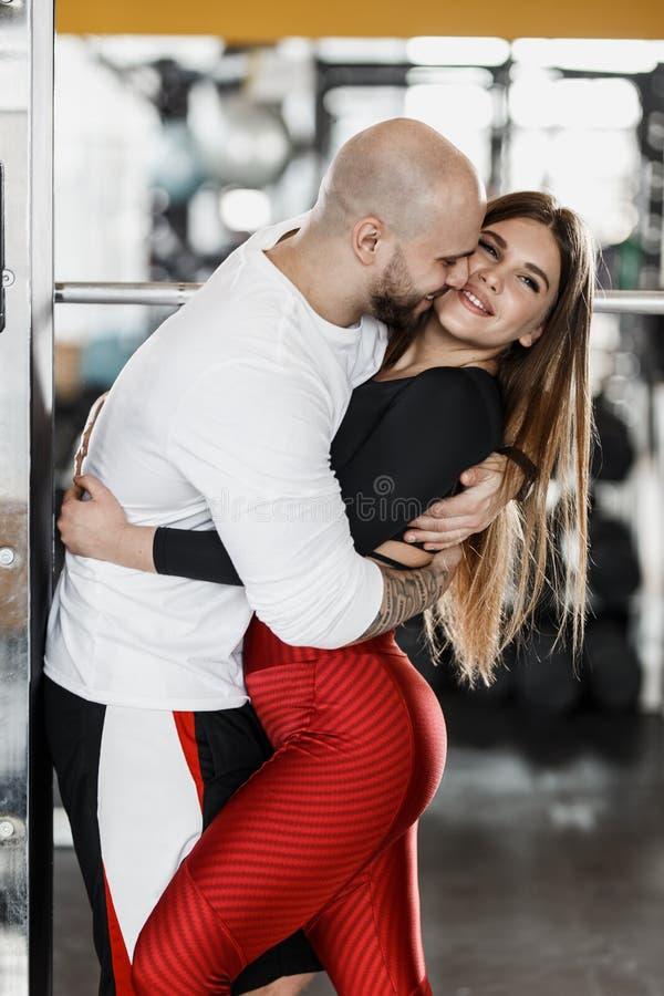 Couples sportifs heureux romantiques L'homme fort et la belle fille mince étreignent dans le gymnase moderne à côté du sport photographie stock libre de droits