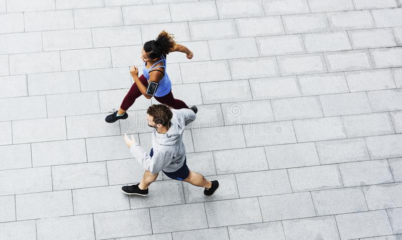 Couples sportifs s'exerçant dehors ensemble image stock