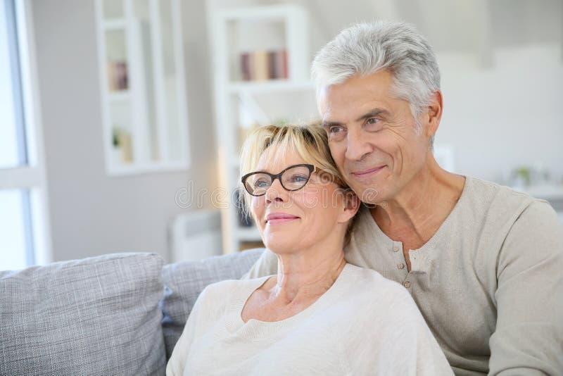 Couples supérieurs à la mode heureux à leur nouvelle maison photographie stock libre de droits