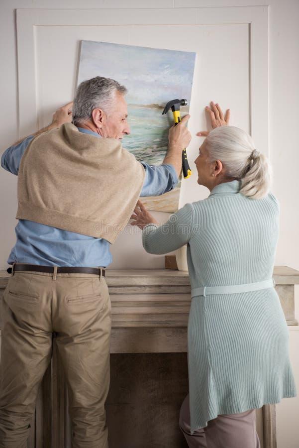 Couples supérieurs accrochant ensemble la photo sur le mur à la nouvelle maison image libre de droits