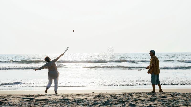 Couples supérieurs actifs jouant la boule de ballon de chi de tai à la plage photos stock