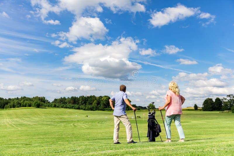 Couples supérieurs actifs jouant le golf sur un cours images stock