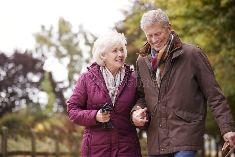 Couples supérieurs actifs sur la campagne d'Autumn Walk On Path Through image libre de droits