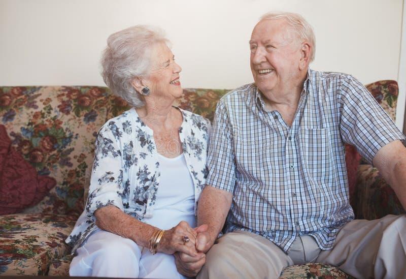 Couples supérieurs affectueux se reposant ensemble à la maison photographie stock
