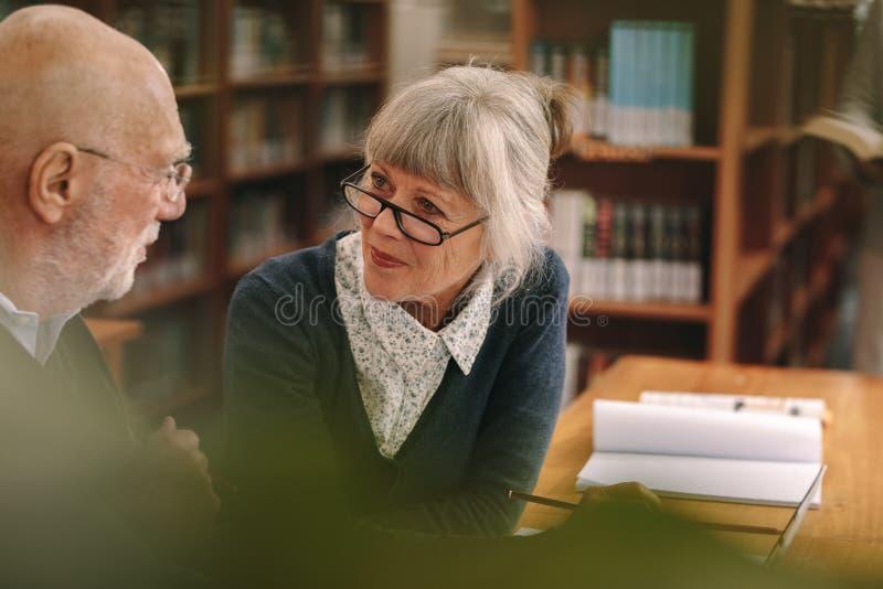 Couples supérieurs agissant l'un sur l'autre les uns avec les autres se reposant dans une bibliothèque photo libre de droits