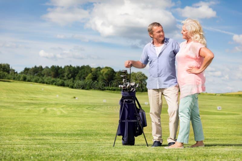 Couples supérieurs appréciant le jeu de golf image stock