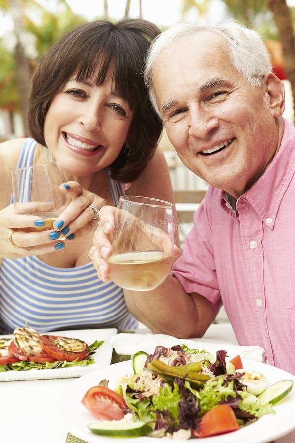 Couples supérieurs appréciant le repas dans le restaurant extérieur ensemble images stock