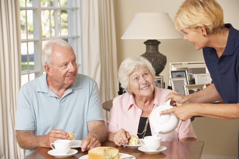 Couples supérieurs appréciant le thé d'après-midi ensemble à la maison avec l'aide familiale photo stock