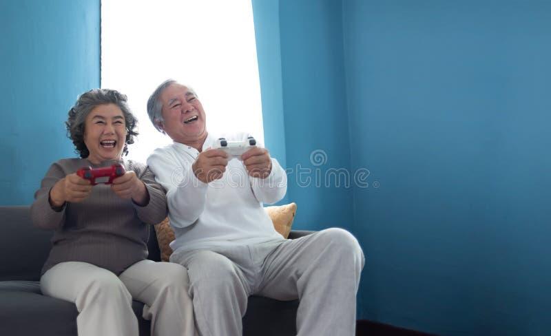 Couples supérieurs asiatiques joyeux jouant des jeux photographie stock libre de droits
