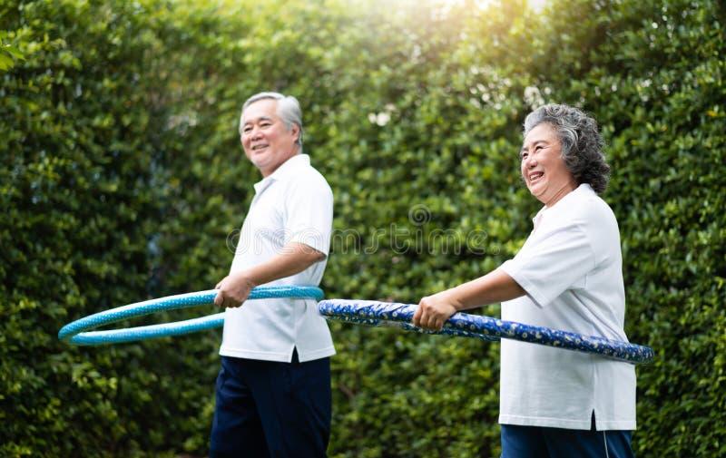 Couples supérieurs asiatiques s'exerçant avec des cercles de danse polynésienne photographie stock