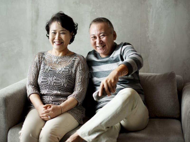 Couples supérieurs asiatiques se reposant ensemble au sofa photo stock