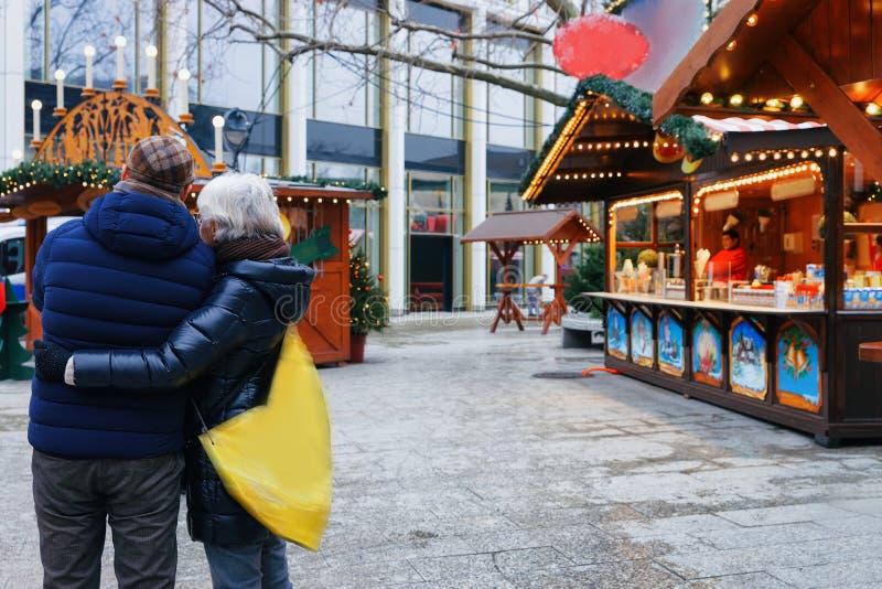 Couples supérieurs au marché de Noël chez Kaiser Wilhelm Memorial Church en hiver Berlin, Allemagne Advent Fair Decoration et sta image libre de droits