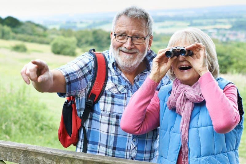 Couples supérieurs augmentant dans la campagne regardant par des jumelles photos libres de droits