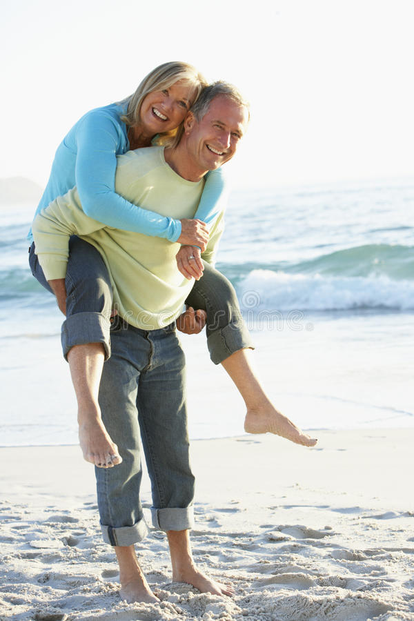 Couples supérieurs ayant Bck porcin sur Sandy Beach photo stock