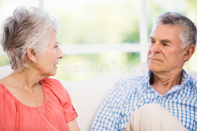 Couples supérieurs ayant l'argument sur le sofa photos libres de droits
