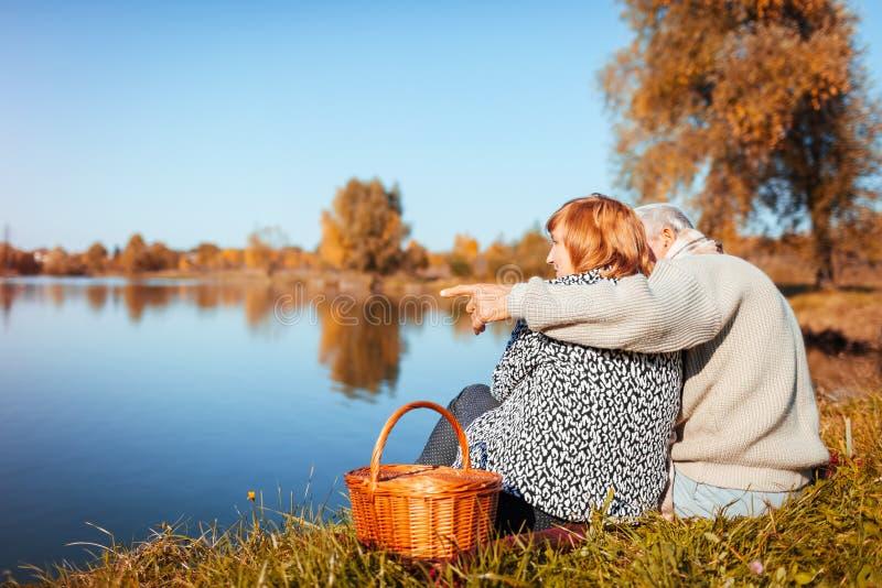 Couples supérieurs ayant le pique-nique par le lac d'automne Homme heureux et femme appréciant la nature et étreindre photo libre de droits
