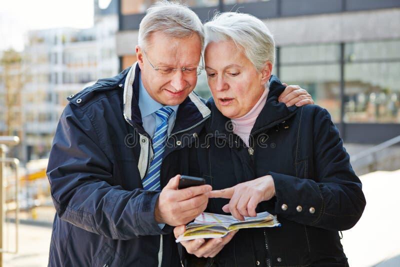 Couples supérieurs comme touristes avec la carte photos stock