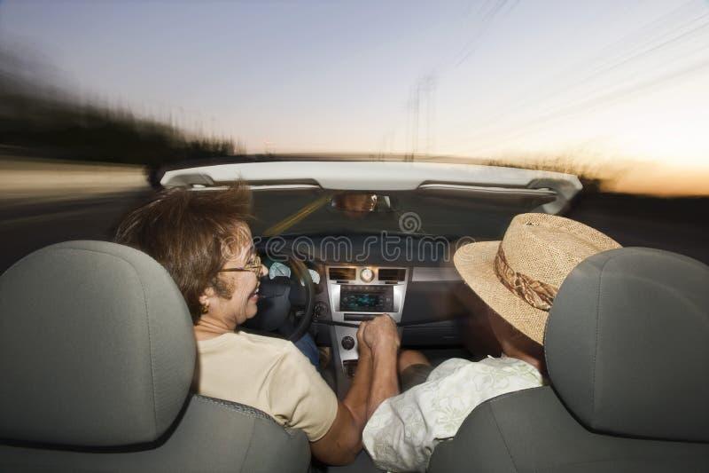 Couples supérieurs conduisant le convertible photo stock