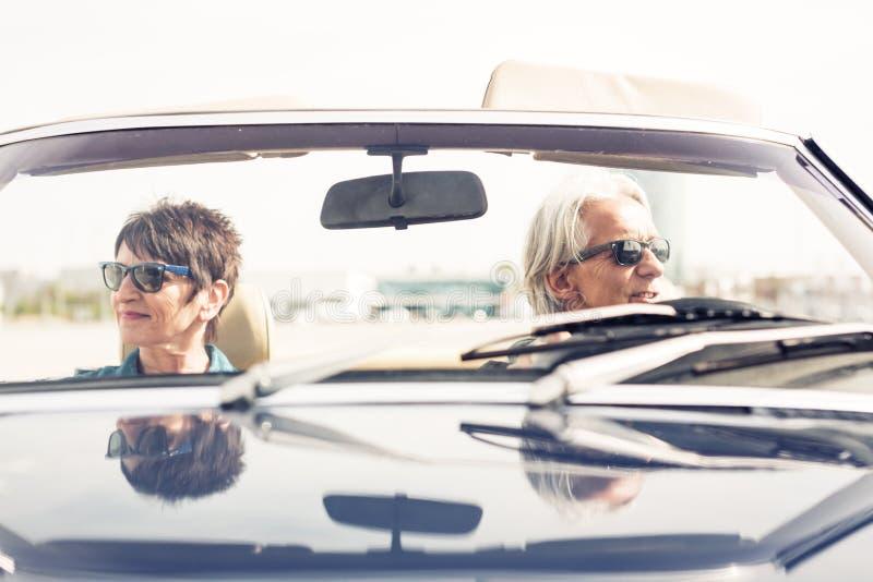 Couples supérieurs conduisant une voiture classique convertible photos stock