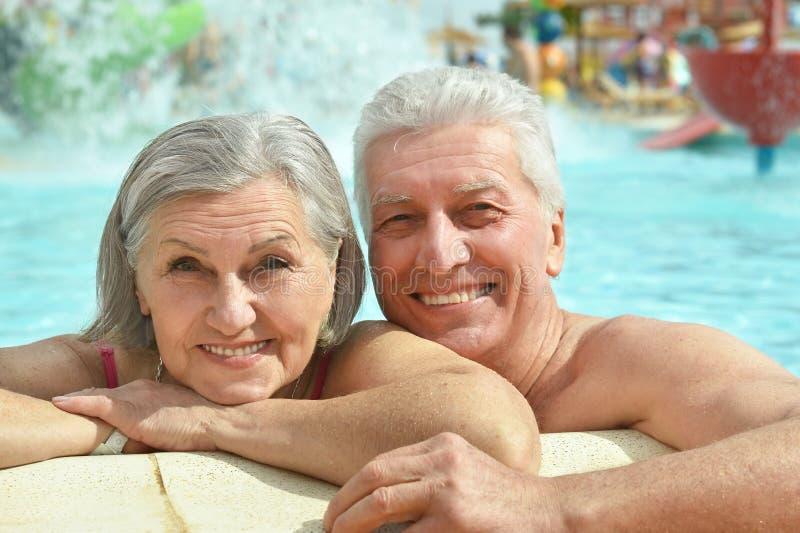 Couples supérieurs détendant à la piscine images stock